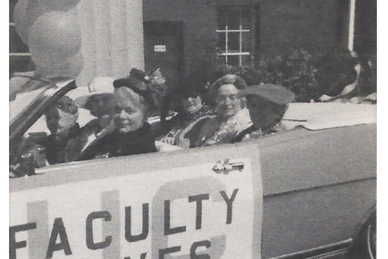 "ID: grayscale photo of 5 women in a hoodless car adorned with a sign that reads ""UC faculty's wives"""