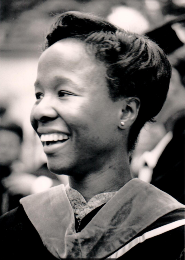 ID: grayscale photo of Arlene Cole-Rhodes at hooding ceremony for PhD, smiling into the distance
