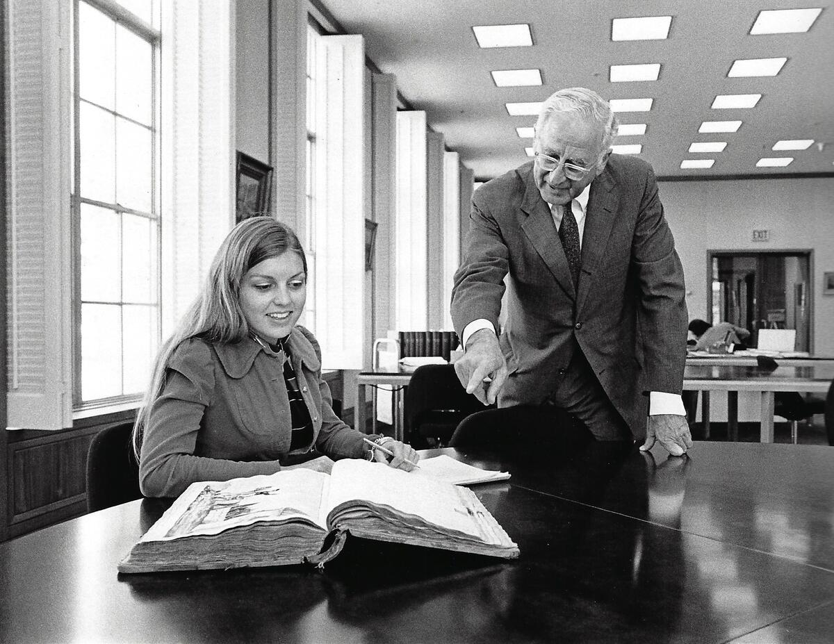 ID: Suzanne Calpestri smiling and taking notes in the Bancroft library, a man in a suit pointing.