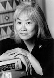 grayscale headshot of writer and alumna Maxine Hong Kingston, posed with books