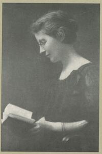 grayscale side profile of Anna Head with glasses, looking downwards at an open book in her hands