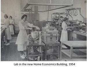 grayscale photo of 4 women wearing aprons in the lab of the new home economics building, which resembles an industrial kitchen; the foremost woman is mixing a large pot