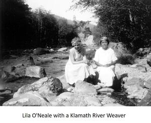 photo of Lila O'Neale in long white dress sitting next to Klamath River Weaver in white gown amongst rocks by a riverbed