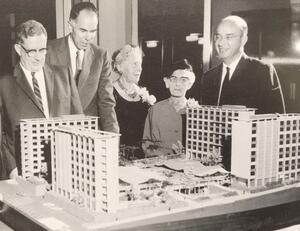 former Dean of Women Mary Blossom Davies and Alice Deutsch standing with 3 other men in front of a miniature model of the unit 1 dorms