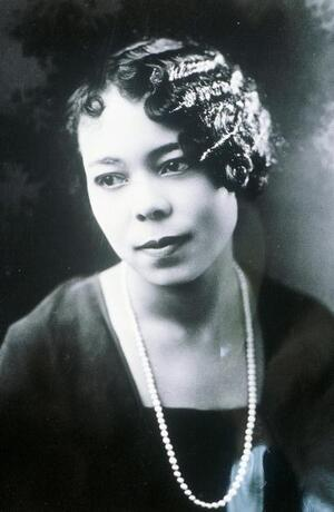 cool toned grayscale portrait of Vivian Osborne Marsh looking into the distance, haired styled in short waves, wearing pearls and black dress