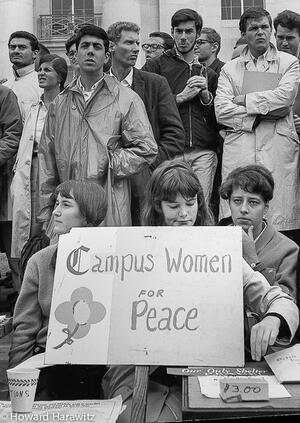 """three women tabling with a sign that reads """"campus women for peace"""" a group of men standing behind them"""
