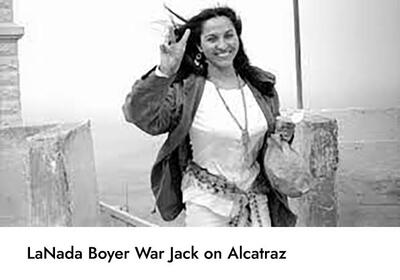 photo of LaNada Boyer War Jack smiling in jacket and cultural necklace while holding up a peace sign on Alcatraz