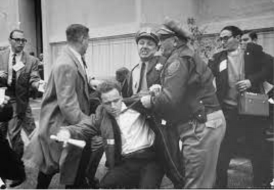 image of Mario Savio being dragged away by 2 policemen as concerned audience members rush to his aid
