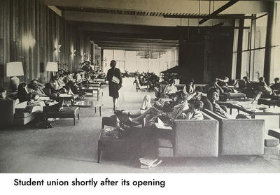 image of a crowded student union shortly after its opening; there are groups of tables and seats occupied by dozens of students