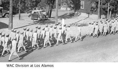 image of WAC division at Los Alamos, dozens of women in uniform marching rank and file down the street